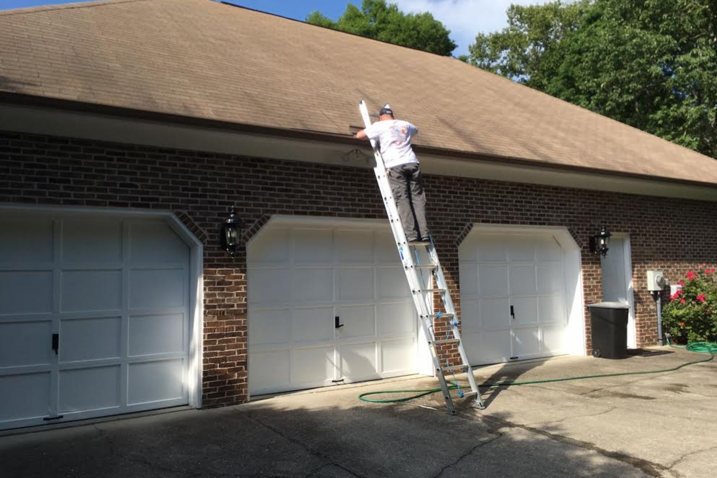 working on a ladder to clean gutters