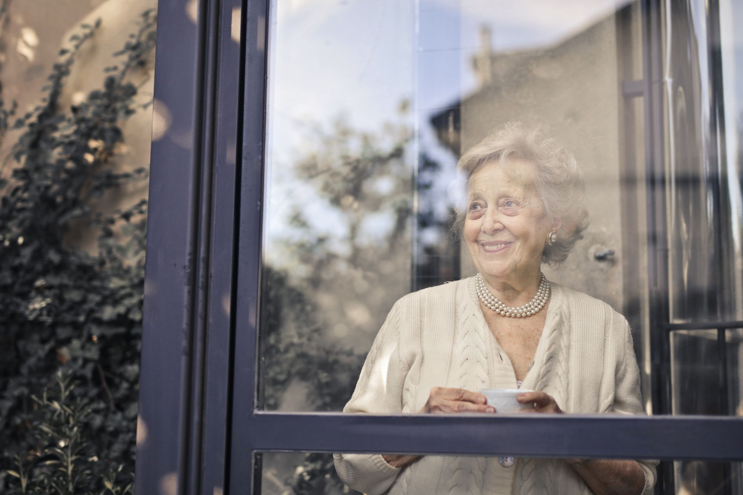 senior looking out home window