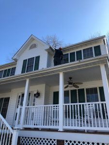 local technician cleaning a gutter on second floor