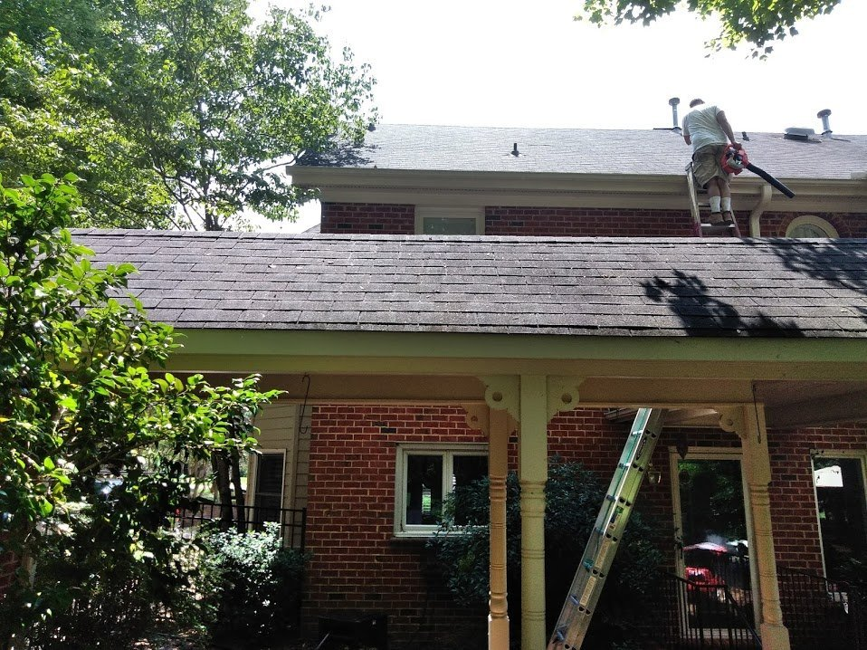 tech cleaning gutter on roof
